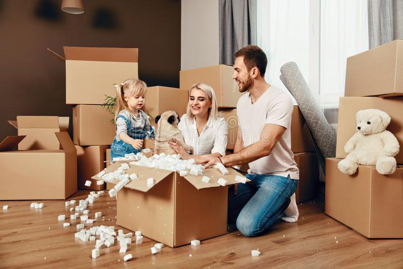 Familien-Bewegen Glückliche Menschen mit Kästen in der neuen Wohnung lizenzfreies stockbild