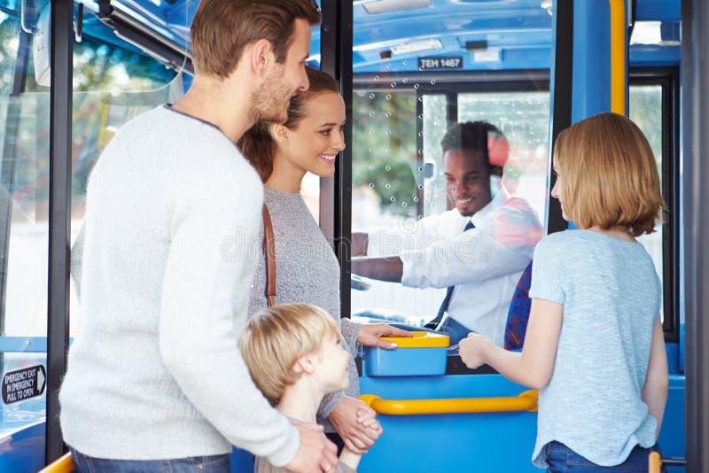 Familien-Einstieg-Bus und Kaufen-Karte stockfotografie