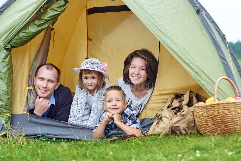 Familien-Eltern und zwei Kinder im Lagerzelt Glückliche Mutter, Vater, Sohn und Tochter auf Sommerferien lizenzfreies stockfoto