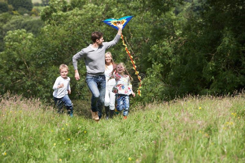 Familien-Fliegen-Drachen in der Landschaft lizenzfreies stockbild