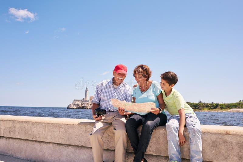 Familien-Großeltern, die touristische Karte in Habana Kuba lesen stockbild