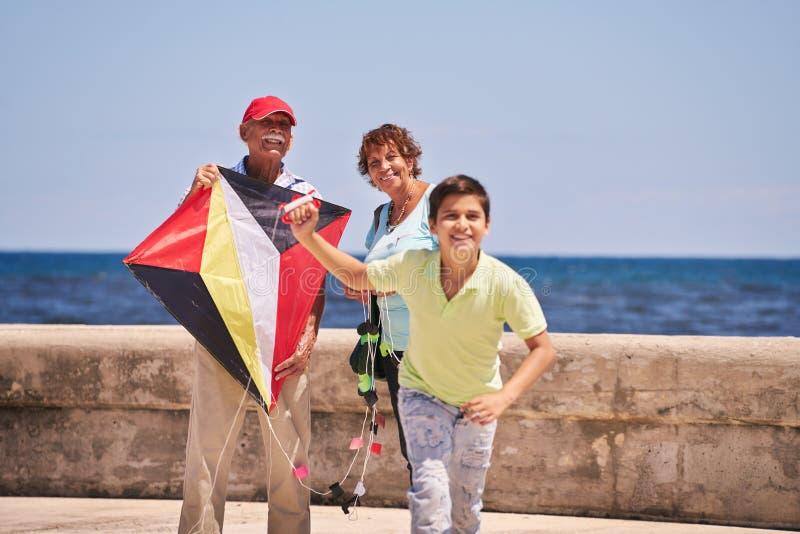 Familien-Junge und Großeltern, die Drachen nahe Meer fliegen stockfotografie