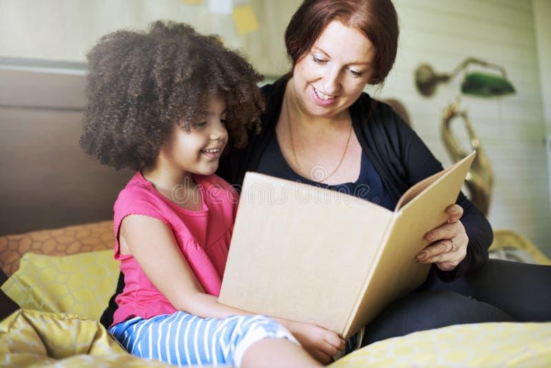 Familien-Kindertochter-Lesebuch-Schlafzimmer-Konzept lizenzfreies stockfoto