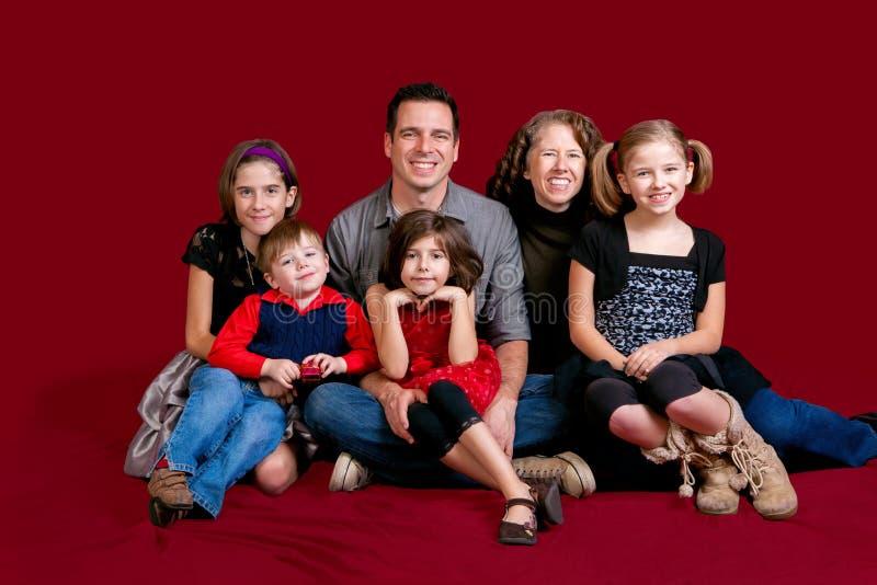 Familien-Porträt auf Rot lizenzfreie stockfotos