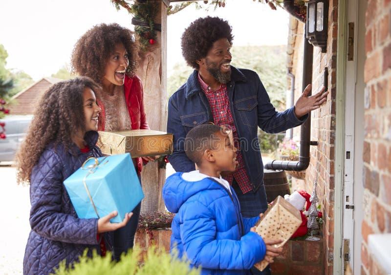 Familien-Stellung bei Front Door As They Arrive für Besuch am Weihnachtstag mit Geschenken lizenzfreie stockfotografie