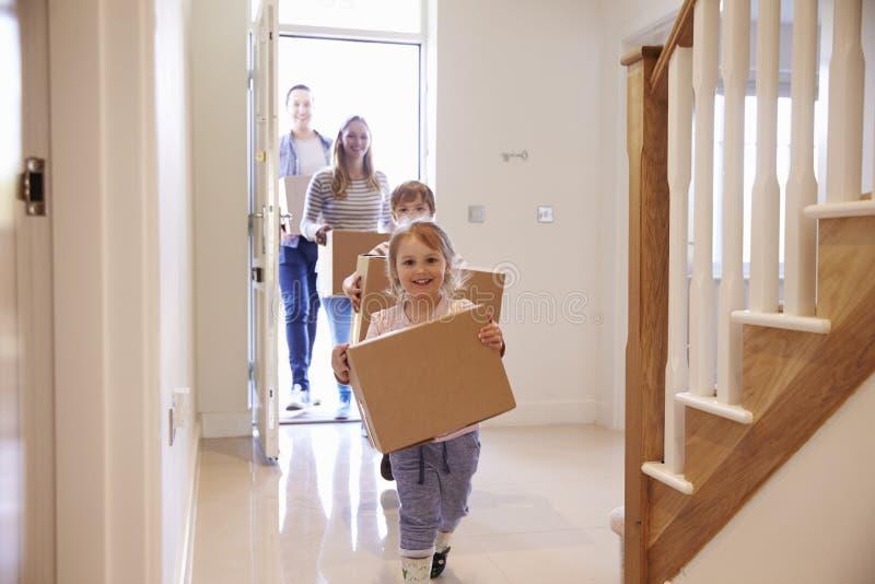 Familien-tragende Kästen in neues Haus an beweglichem Tag lizenzfreie stockbilder