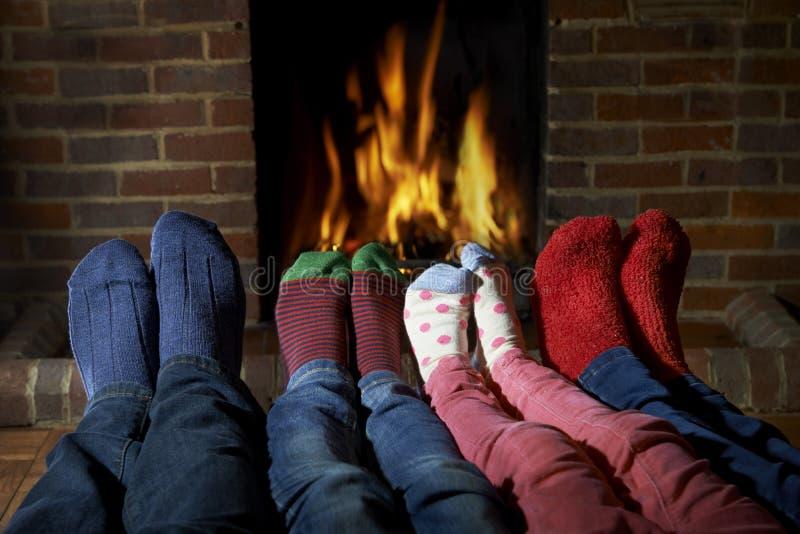Familien-tragende Socken, die Füße durch Feuer wärmen stockbild