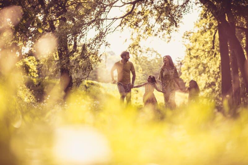 Familien-Zeit Glückliche Eltern mit ihren kleinen Mädchen in der Natur lizenzfreie stockfotos