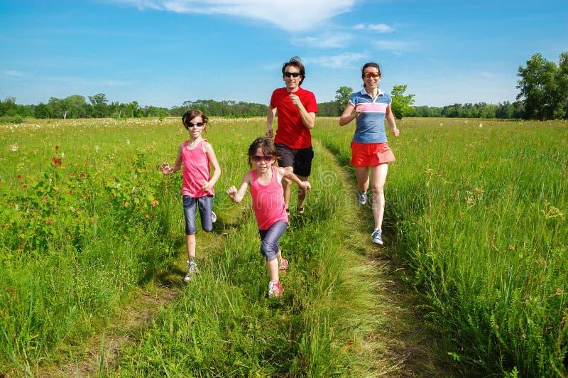Familieneignung draußen, Eltern mit den Kindern, die im Park, zusammen laufend rütteln lizenzfreies stockfoto