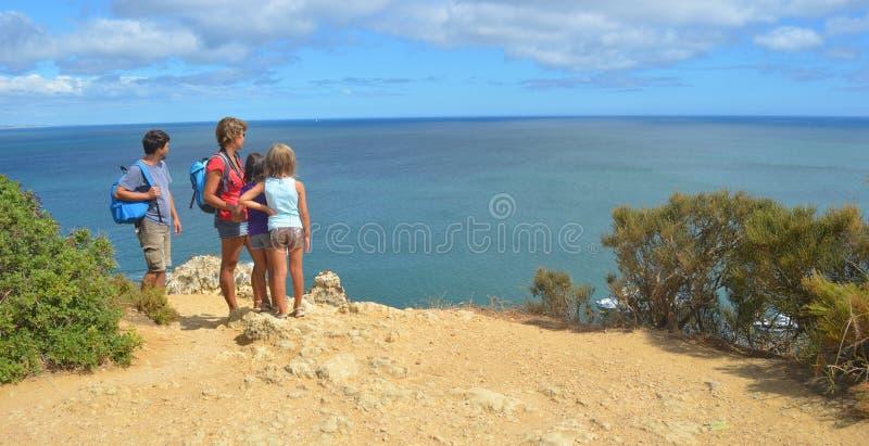 Familienerwachsene und -kinder, die heraus Ansicht von der Klippe zum Meer betrachten stockbild
