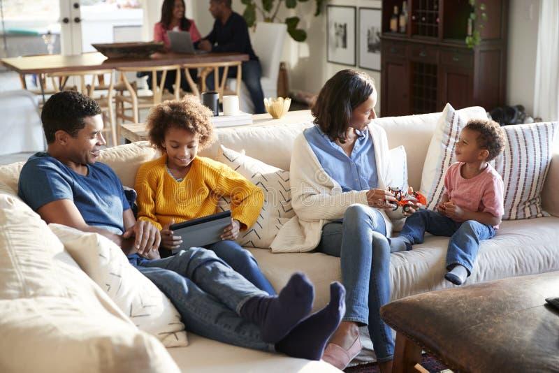 Familienfamilie mit drei Generationen, die Zeit in ihrem Großraumwohnzimmer, Großeltern im Hintergrund, erhöhte Ansicht verbringt stockfoto
