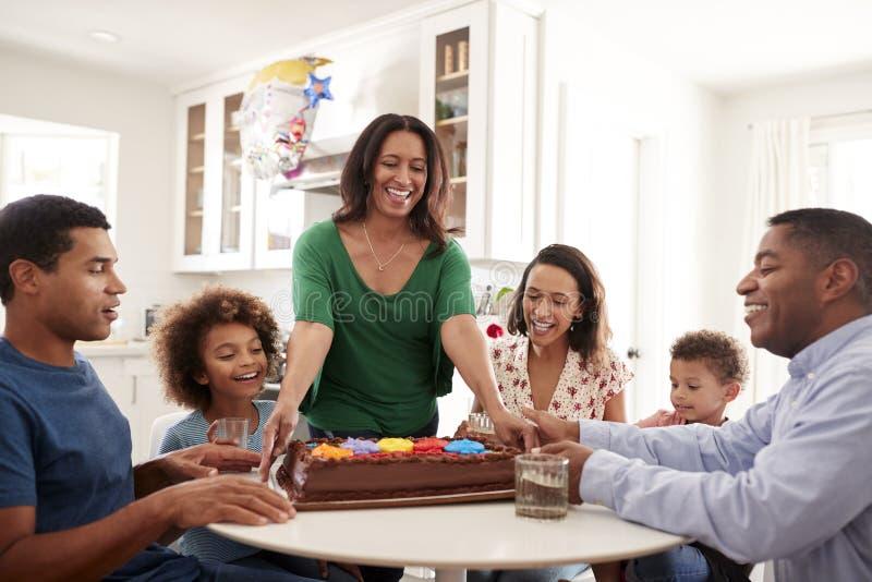 Familienfamilie mit drei Generationen, die zusammen in der Küche feiert einen Geburtstag, Großmutter holt den Kuchen zum Tabelle  lizenzfreie stockbilder