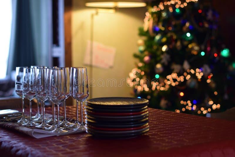 Familienfeiertabelle mit Champagnergläsern und Staplungsplatten auf Weihnachtsbaumhintergrund lizenzfreie stockbilder