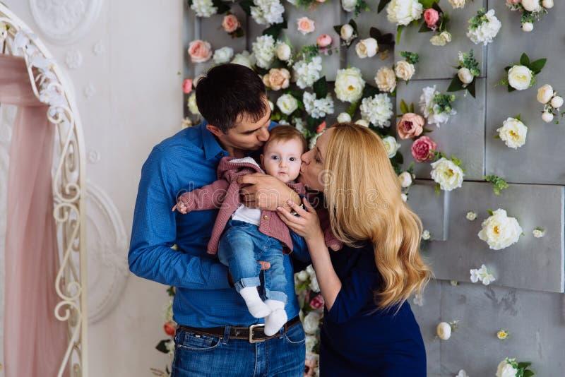 Familienfotoeltern halten ihre kleine Tochter in ihren Armen und in Kuss auf beiden Backen Elterliche Sorgfalt und Wärme von stockbilder