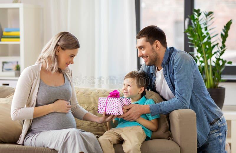 Familiengeben der schwangeren Mutter vorhanden zu Hause stockfotos