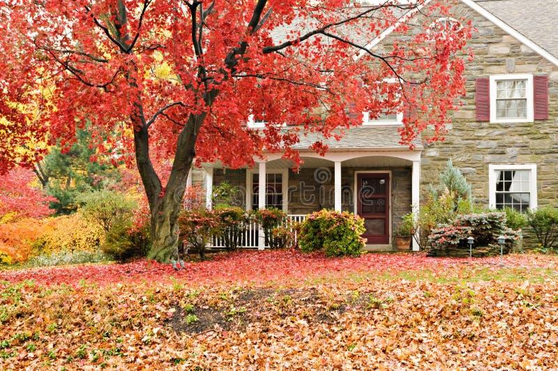 Familienhaus mit vorderem Rasen in den Fallfarben stockfotografie