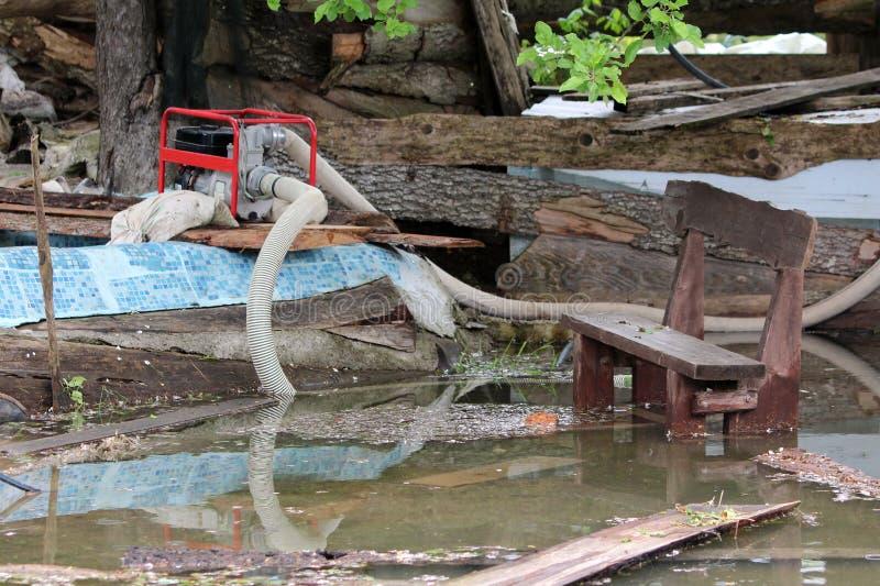 Familienhaushinterhof vollständig zerstört während der Naturkatastrophe mit der industriellen Treibstoffwasserpumpe benutzt, um d stockfoto