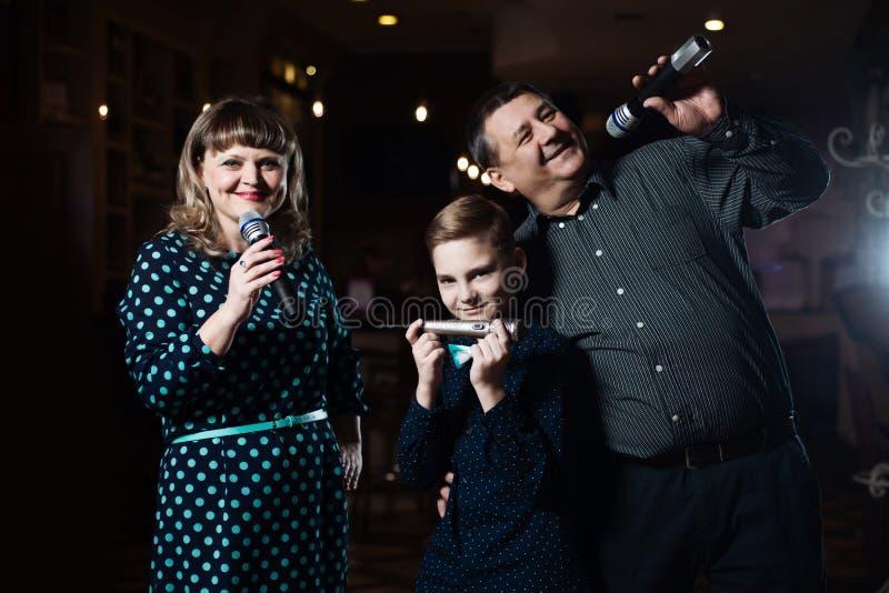 Familienkaraoke Porträt einer glücklichen Familie, singend in den Mikrophonen lizenzfreie stockbilder