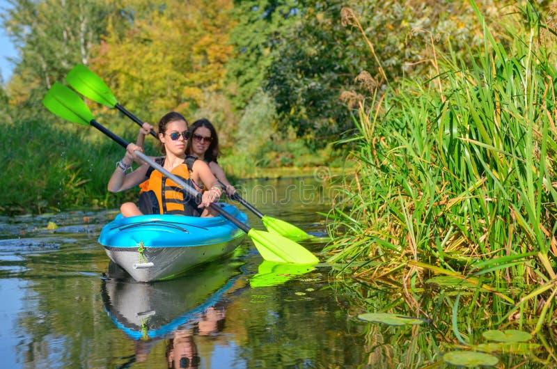 Familienkayak fahren, Mutter und Kind schaufelnd im Kajak auf Flusskanuausflug, aktives Herbstwochenende und -ferien, Sport und E stockfotografie