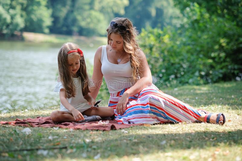 Familienkonzept: Mutter und Tochter, die im Park sitzen Verständigen mit Kind stockfotografie