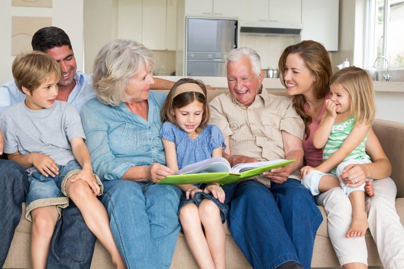 Familienlesemärchenbuch im Wohnzimmer lizenzfreies stockfoto