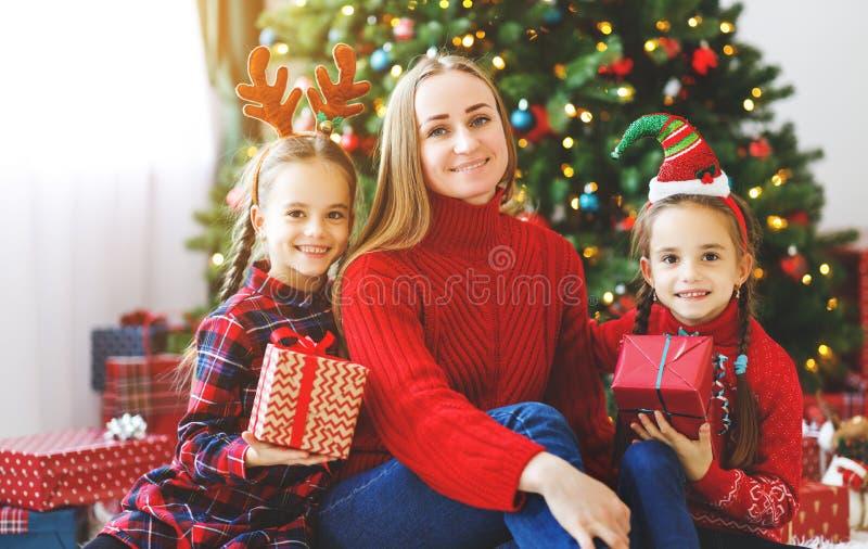 Familienmutter und Kinderoffene Geschenke auf Weihnachtsmorgen stockfotografie