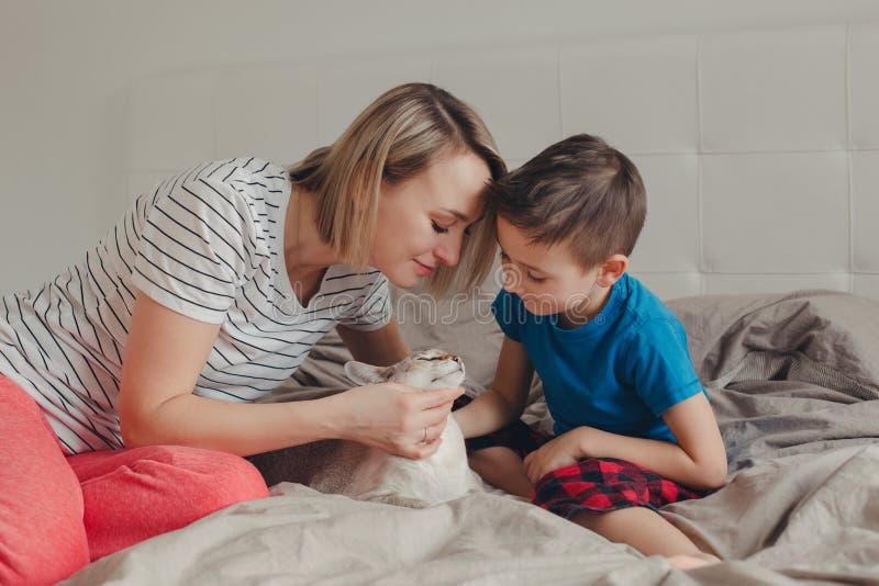 Familienmutter und -sohn, die zu Hause auf Bett im Schlafzimmer sitzen und orientalische Punkt-farbige Katze streicheln stockbild