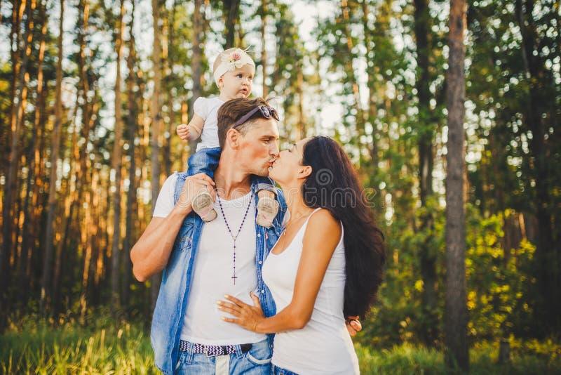 Familienmutter, -vati und -tochter sitzt am Vati auf den Schultern und am Elternkuß auf der Natur im Wald im Sommer an der Sonne stockbild