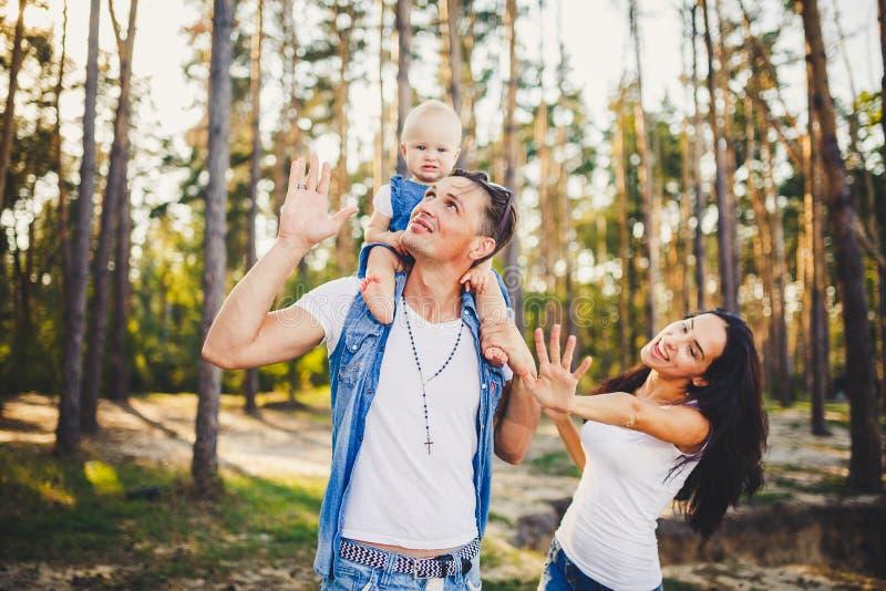 Familienmutter, -vati und -tochter sitzt am Vati auf den Schultern und am Elternkuß auf der Natur im Wald im Sommer an der Sonne lizenzfreies stockfoto