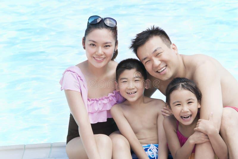 Familienporträt, -mutter, -vater, -tochter und -sohn, lächelnd durch das Pool lizenzfreies stockbild