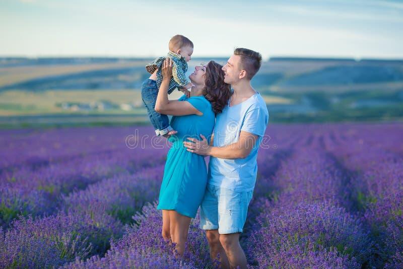 Familienporträt-Muttervater und Babysohn auf dem Lavendelfeld, das Spaß zusammen hat Glückliches Paar mit Kind das Ferientragen g lizenzfreie stockfotografie