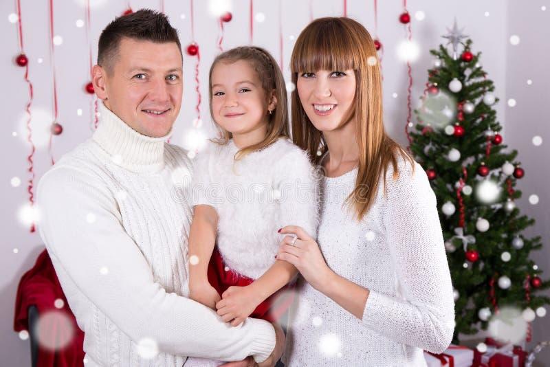 Familienporträt von glücklichen Eltern und von Tochter mit Weihnachten-tre lizenzfreie stockfotos