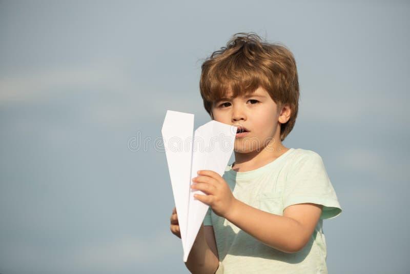 Familienreise und Ferienkonzept Gl?ckliches Kind, das mit Spielzeugflugzeug gegen Sommerhimmelhintergrund spielt Gl?ckliches Kind lizenzfreies stockfoto