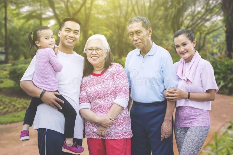 Familienstellung mit drei Generationen im Park stockbilder