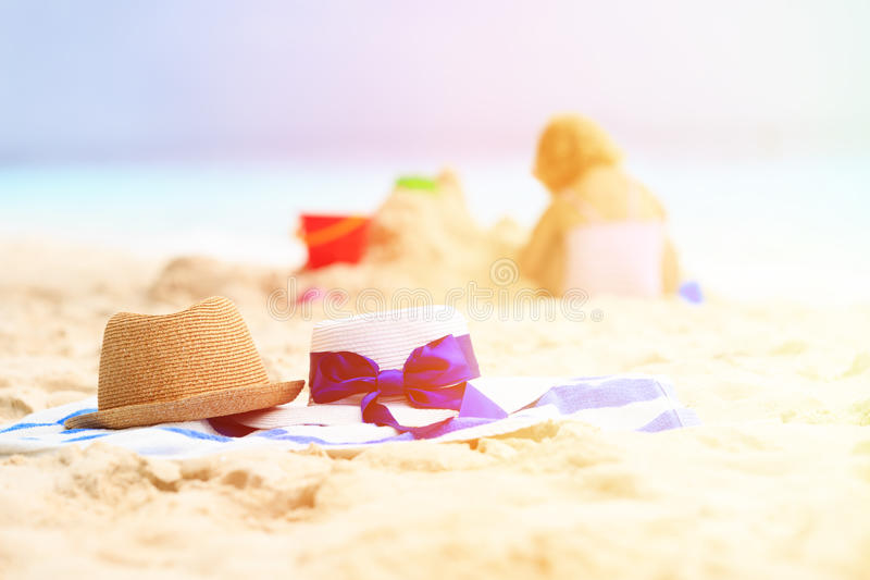 Familienstrand-Ferienkonzept - Hüte und Kind spielen stockfotos