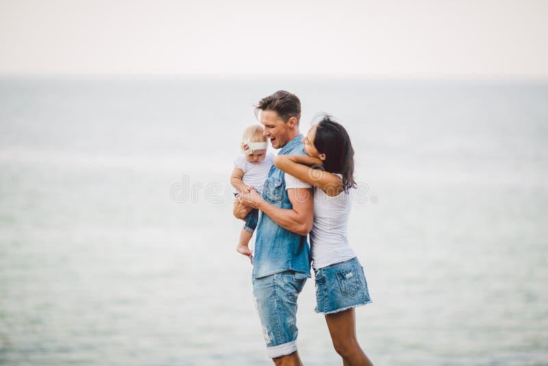 Familienurlaub in der Natur Drei, Mutter, Vati, Tochter ein Jahr, das mit Rückseiten auf Unterlassungsmeer der Klippe steht Mann, stockbild