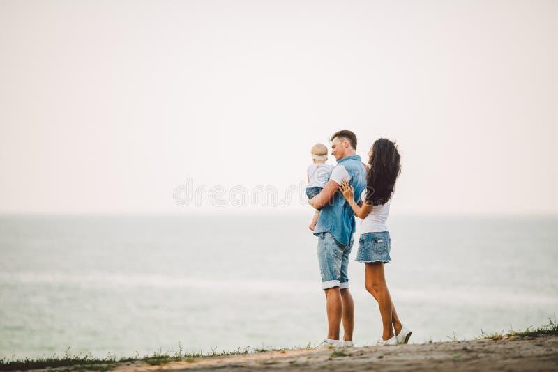 Familienurlaub in der Natur Drei, Mutter, Vati, Tochter ein Jahr, das mit Rückseiten auf Unterlassungsmeer der Klippe steht Mann, lizenzfreie stockfotos
