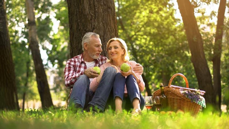 Familienwochenende, Paar im Ruhestand, das im Park sitzt und grüne Äpfel, Picknick isst lizenzfreies stockbild