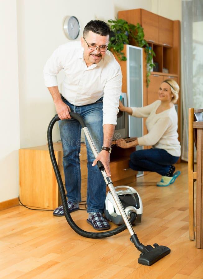 Familiepaar die thuis schoonmaken stock afbeelding