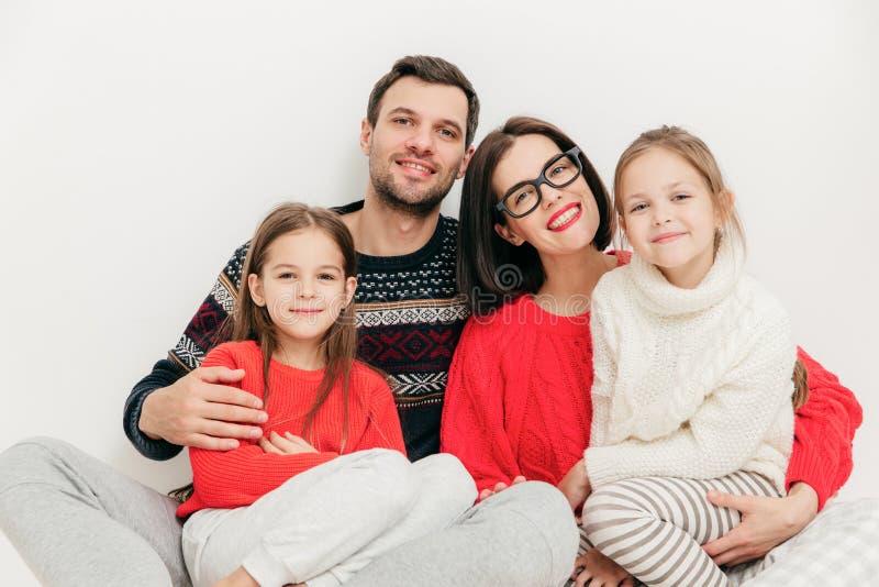 Familieportret: de moeder, de vader en twee zusters kijken direct binnen stock foto's