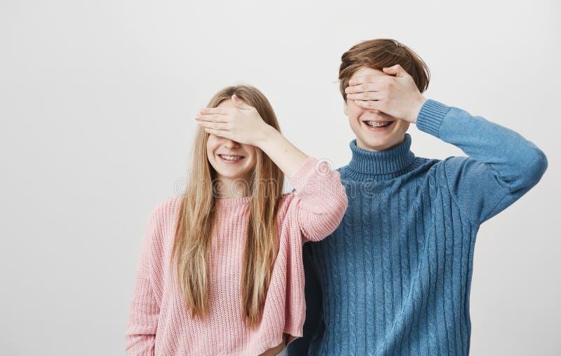 Familieportret die van broer en zuster tegen grijze muur, met steunen glimlachen Jong blond mannetje in blauwe sweater en stock afbeeldingen