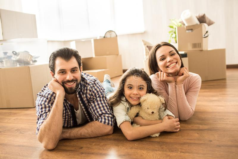 Familieportret die van drie mensen op de vloer liggen De man, de vrouw en hun dochter kijken vrolijk en gelukkig Er zijn stock fotografie