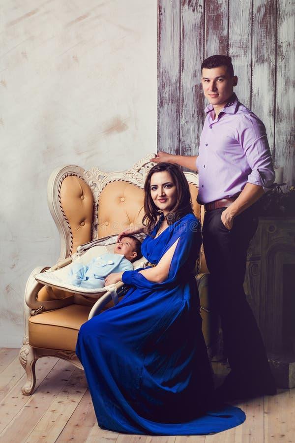 Familieportret in een luxueuze binnenlandse vader en een moeder en a royalty-vrije stock afbeeldingen
