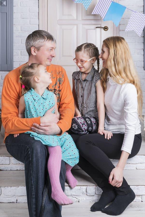 Familieportret op portiek van het huis stock foto's