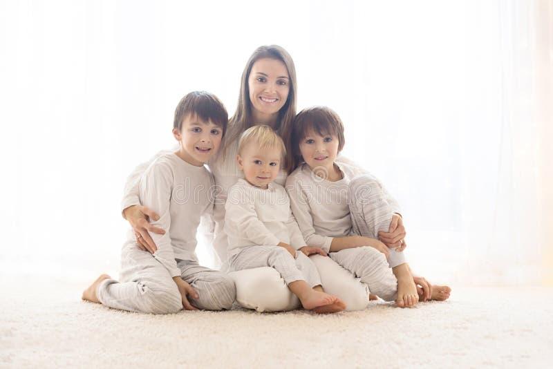 Familieportret van moeder en haar drie die jongens, op wit, achterlicht wordt geïsoleerd royalty-vrije stock fotografie