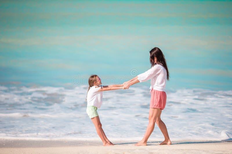 Familiepret op wit zand Glimlachende moeder en het aanbiddelijke kind spelen bij zandig strand op een zonnige dag stock afbeeldingen