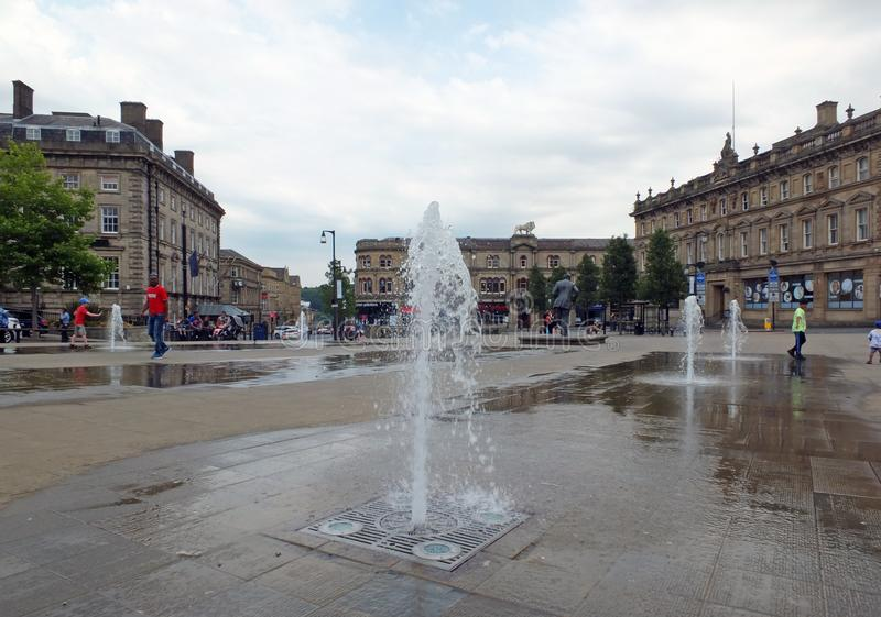 Families and children playing in the fountains in the pedestrian St. George`s Square in huddersfield yorkshire. Huddersfield, Yorkshire, England - Juiy 28 2018 royalty free stock photo