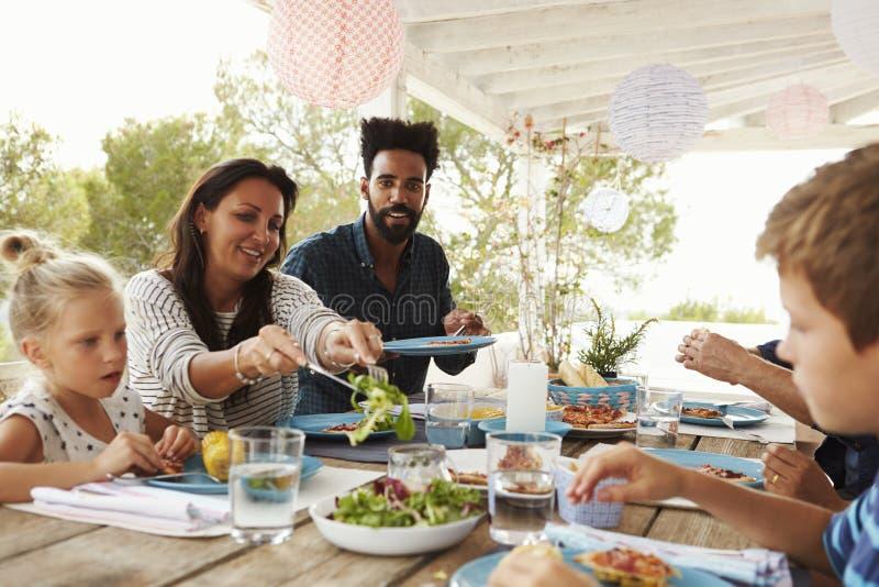 Families die van Openluchtmaaltijd op Terras samen genieten royalty-vrije stock afbeelding