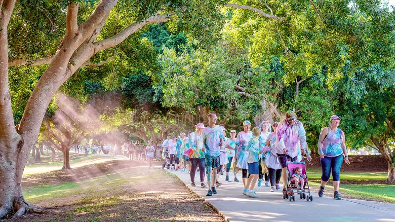Families Happily Participate In Color Frenzy Fun Run. MACKAY, QUEENSLAND, AUSTRALIA - JUNE 2019: Pink powder fills the air as unidentified rainbow costumed royalty free stock photography