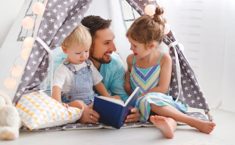 Familievader die aan kinderenboek thuis lezen in tent stock afbeelding